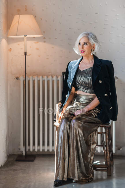 Magnificent senior woman in simple interior with floor lamp — Stock Photo