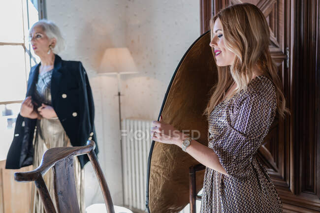 Carefree confident young woman against puzzled senior lady — Stock Photo