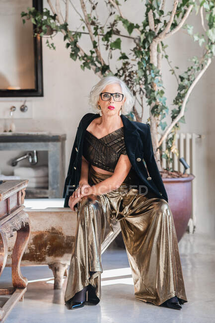 Serious bossy elderly woman in luxurious outfit against vintage interior bathroom — Stockfoto