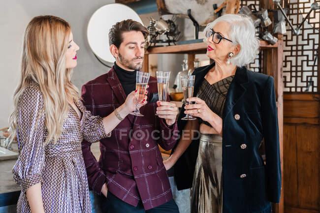 Витончені ділові партнери смажать з флейтою шампанського, відзначаючи успіх — стокове фото