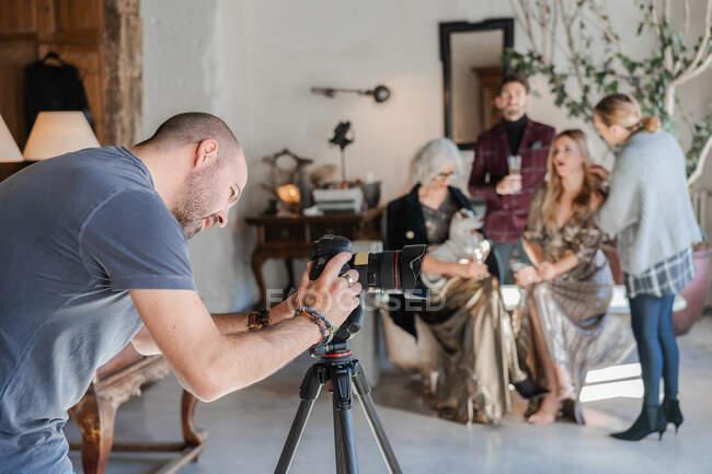 Fotógrafo instalando equipos mientras compañero de trabajo asistente preparando a los clientes para el rodaje en el estudio de fotografía contemporánea - foto de stock