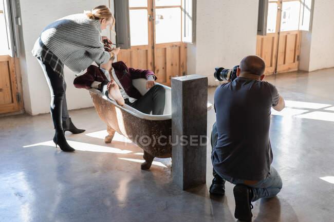 Fotógrafo se preparando para atirar com câmera enquanto colega de trabalho aplicando maquiagem no modelo deitado no banho no estúdio de fotos contemporâneo — Fotografia de Stock