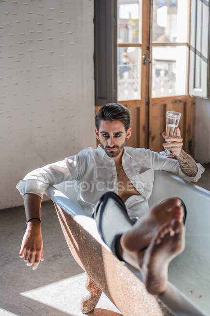Serious cool barefoot rebel in elegant clothes relaxing alone in bathtub and celebrating own success against rustic interior in country house — Stock Photo