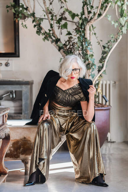 Serious bossy elderly woman in luxurious outfit against vintage interior bathroom — Stock Photo