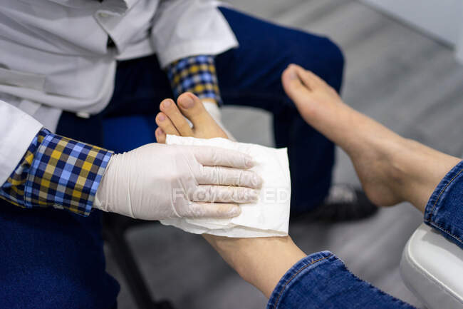 Doctor cleaning feet of patient — Stock Photo