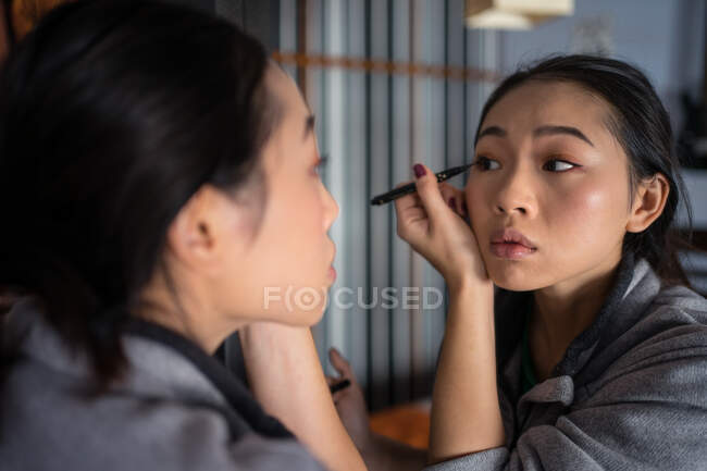 Asian woman applying eyeliner in front of mirror — Stock Photo