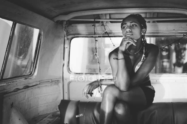 From below of thoughtful dreaming young African American woman sitting in retro van leaning chin on hand and looking away — Stock Photo