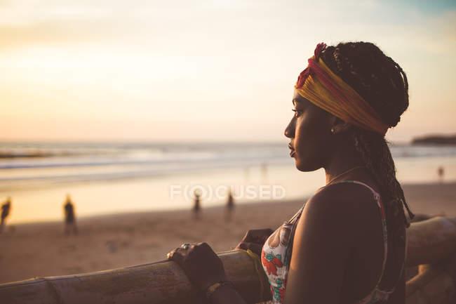 Donna in cappello in piedi sulla spiaggia e godendo paesaggio marino — Foto stock