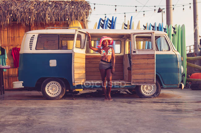 Молода афроамериканська жінка, власник місцевої дошки для серфінгу, одягнена в барвистий кінчик бікіні і капелюх, стоїть поруч з вінтажним фургоном з рядом дошок для серфінгу на задньому плані. — стокове фото