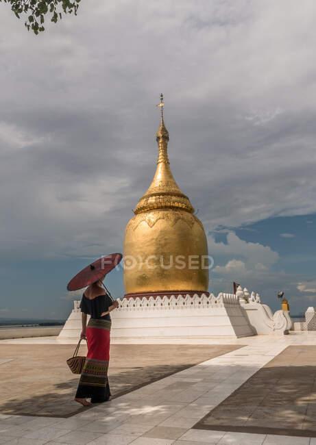 Жінка з традиційною парасолькою йде поруч з буддійською пагодою. — стокове фото