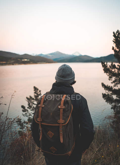Назад погляд людини в капелюсі і теплий піджак з рюкзаком, який насолоджується темною водою, що відбиває небо і скелясті сніжні гори навколо берега. — стокове фото