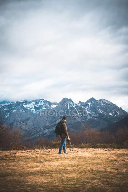 Vista posteriore del viaggiatore in giacca con zaino e macchina fotografica che cammina verso la montagna innevata godendo di visite turistiche — Foto stock