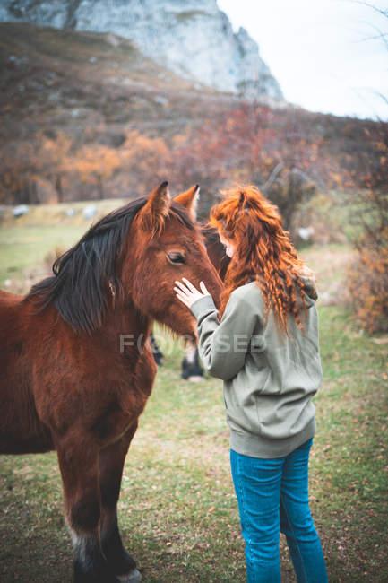 Vista laterale di donna sorridente con lunghi capelli rossi in felpa con cappuccio accarezzando cavallo marrone con criniera nera in pascolo di montagna — Foto stock