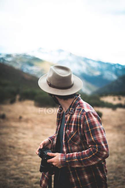 Стильний мандрівник у капелюсі та сорочці з фотокамерою, що дивиться назад на кам