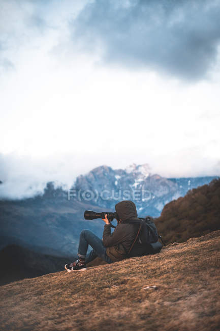 Side view of traveling photographer with backpack taking photo sitting on ground in mountains — Stock Photo