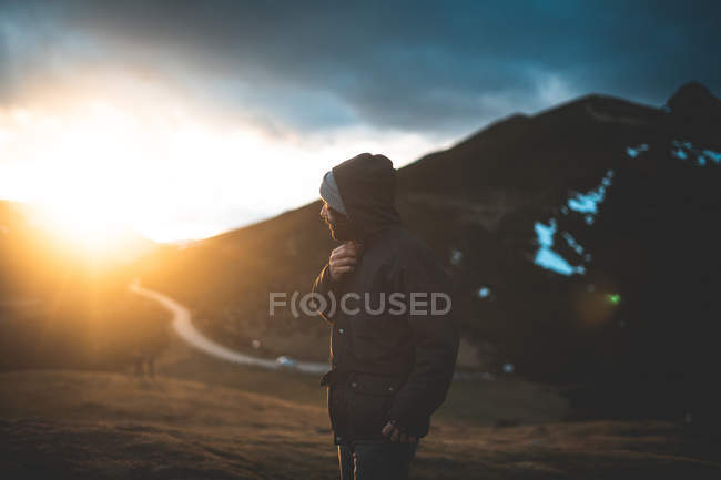 Side view of traveler in jacket with hoodie enjoying landscape of mountain in sunlight — Stock Photo