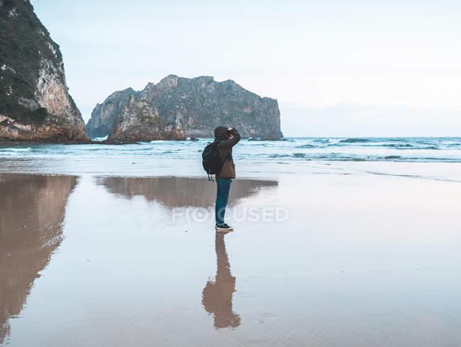 Vista laterale del viaggiatore in giacca con zaino scattante fotografia sul mare circondato da montagna — Foto stock