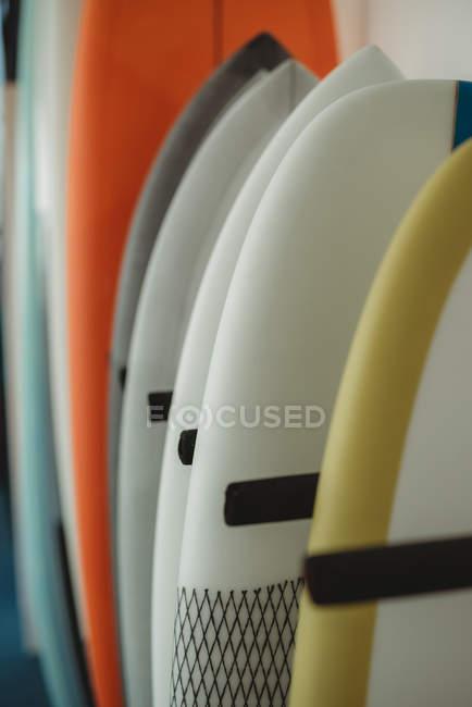 Vielzahl bunter Surf- und Pfützenbretter, reihenweise entlang der Wand angeordnet und mit schwarzen Trennwänden getrennt — Stockfoto