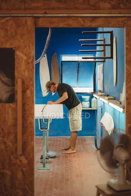 Робітник з вимірюванням стрічки роблять серфінг дошки — стокове фото