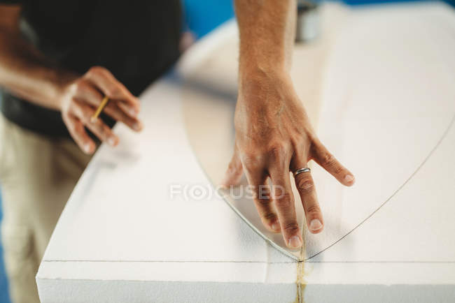 Cropped image of professional male with pencil in hand circling pattern of surf board while working in workshop — Stock Photo