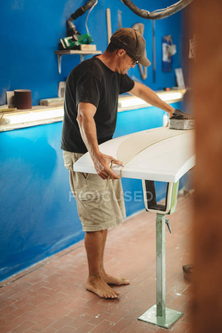 Workman with measuring tape making surf board — Stock Photo
