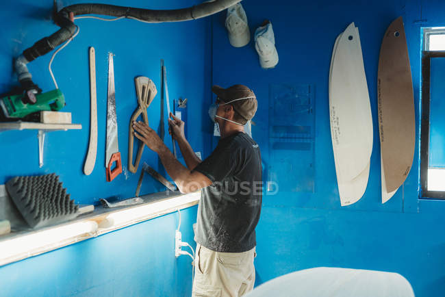 Side view of craftsman in protective mask taking instrument from blue wall while working in workshop and producing surf boards — Stock Photo