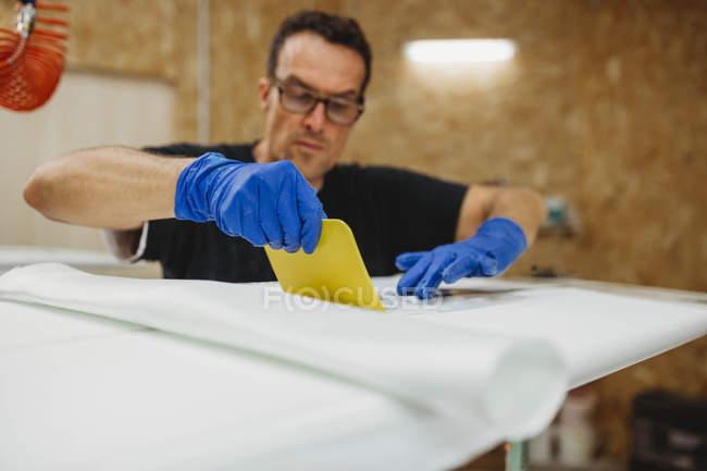 Workman creating surf board — Stock Photo