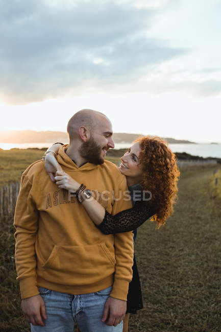 Man embracing by happy curly haired girlfriend in dress and denim vest while standing together on meadow — Stock Photo