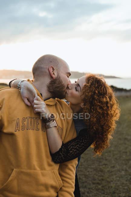 Homme embrassant par heureuse petite amie aux cheveux bouclés en robe et gilet en denim tout en se tenant ensemble sur la prairie, baisers — Photo de stock