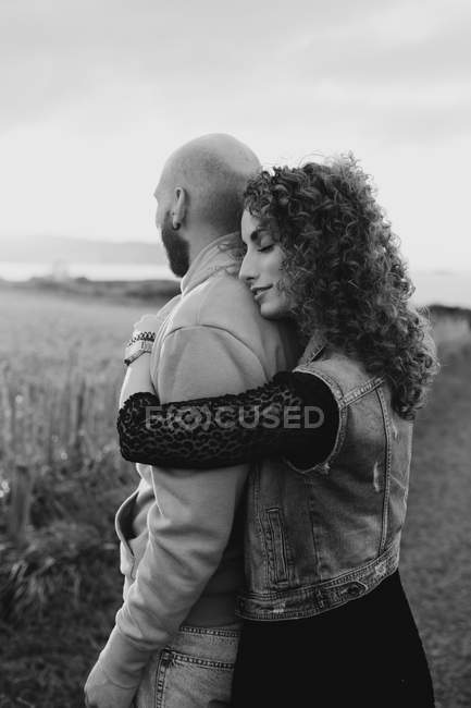 Мужчина обнимает счастливую кудрявую подружку в платье и джинсовом жилете, стоя вместе на лугу — стоковое фото