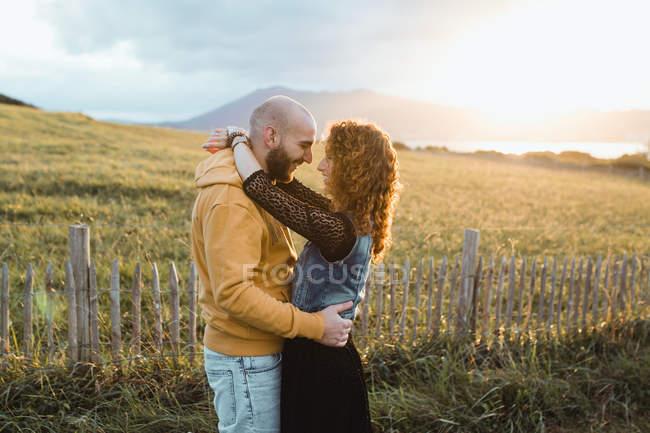 Jeune homme en sweat à capuche jaune embrassant petite amie en robe et gilet en denim tout en se tenant près de la clôture ensemble sur la prairie — Photo de stock