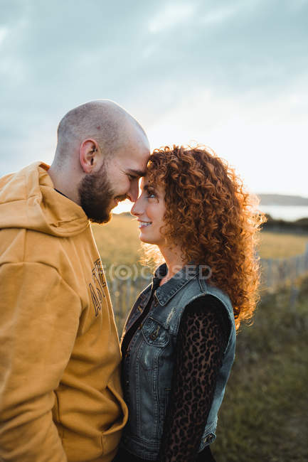 Young man in yellow hoodie embracing girlfriend in dress and denim vest while standing near fence together on meadow — Stock Photo