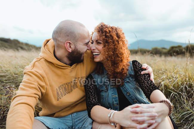 Junger Mann in gelbem Kapuzenpullover umarmt Freundin in Kleid und Jeansweste, während er neben Zaun auf Wiese steht — Stockfoto