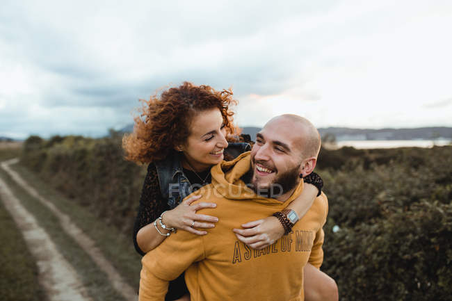 Happy hipster man giving girlfriend piggyback ride while walking on rural road between green farm and sea coast in cloudy day — Stock Photo