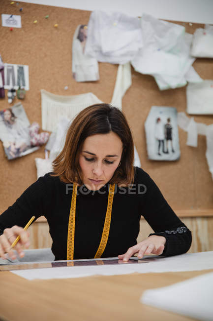 Focused adult woman sitting at table and making cutout while working in professional dressmaking studio — Stock Photo
