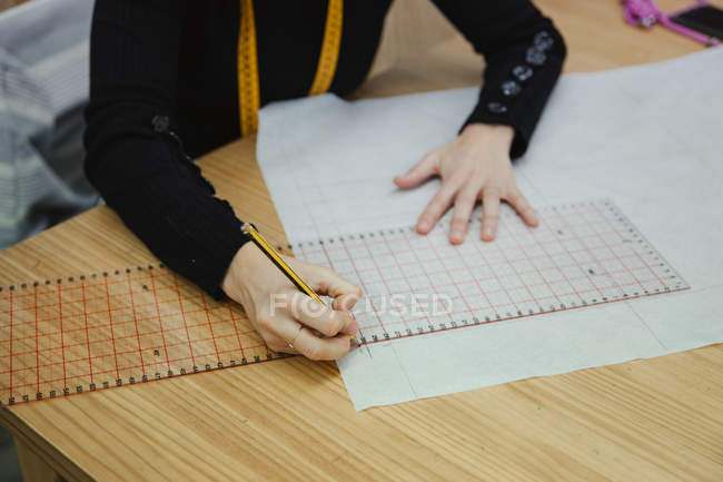 From above focused adult woman sitting at table and making cutout while working in professional dressmaking studio — Stock Photo