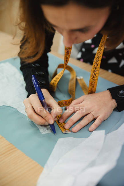 Adult woman using tape to measure garment part on table during work in professional dressmaking workshop — стокове фото