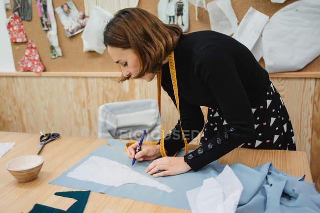Femme adulte utilisant du ruban adhésif pour mesurer la partie vêtement sur la table pendant le travail dans un atelier de couture professionnelle — Photo de stock