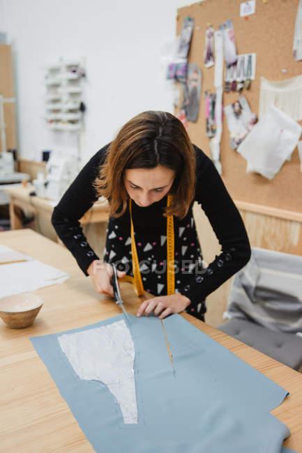 Mulher usando tesouras afiadas para cortar detalhes do vestuário do tecido enquanto se senta à mesa na oficina de alfaiate — Fotografia de Stock