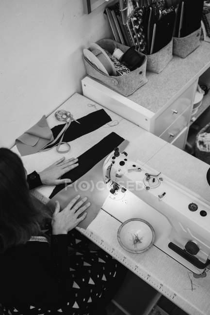 Женщина сидит за столом и делает часть одежды на швейной машине во время работы в профессиональной студии — стоковое фото
