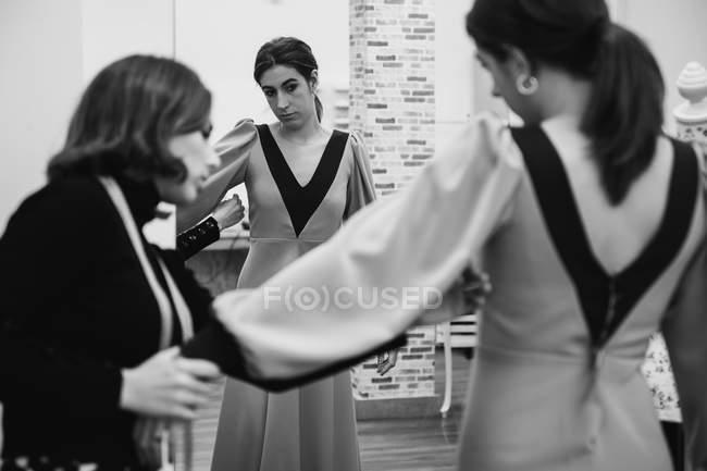 Виробник одягу підбирає традиційну сукню на спині клієнтки під час роботи в професійній майстерні. — стокове фото