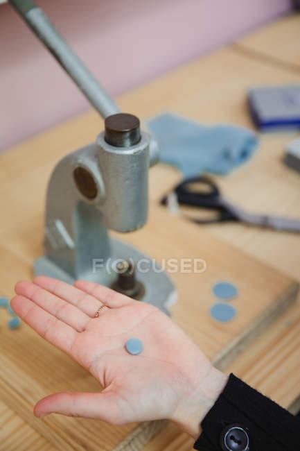 Dall'alto di sartoria dimostrando bottone fatto a mano sopra banco di lavoro in officina professionale — Foto stock