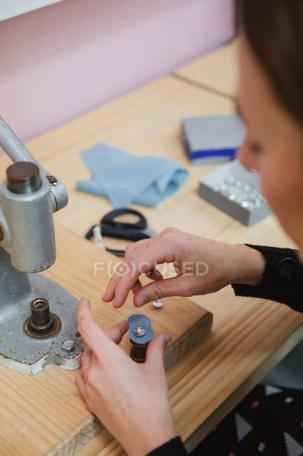 Donna tirando leva del bottoniere sul tavolo in officina di sartoria professionale mentre fa indumento — Foto stock