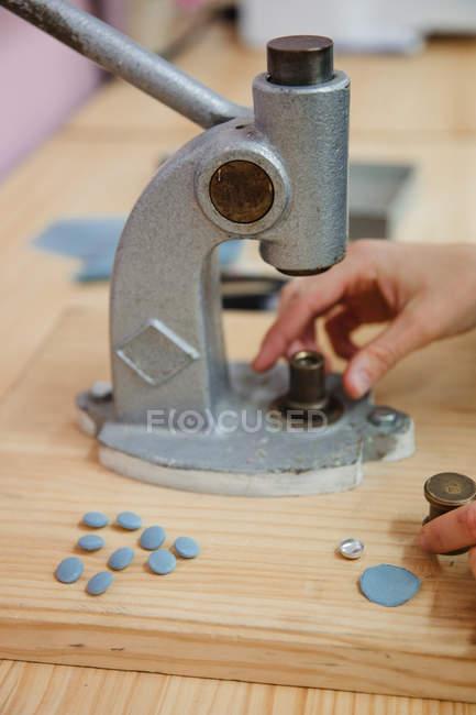 Женщина тянет рычаг пуговицы на стол в профессиональной швейной мастерской при изготовлении одежды — стоковое фото