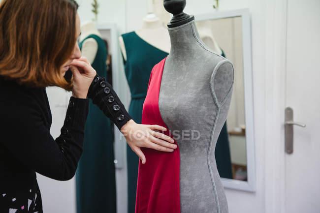 Жінка за допомогою шпильок прикріпляє червону тканину до манекена, одягаючись у професійну кравецьку студію. — стокове фото