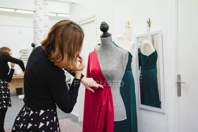 Woman using pins to attach red fabric to mannequin while making dress in professional tailor studio — Stock Photo