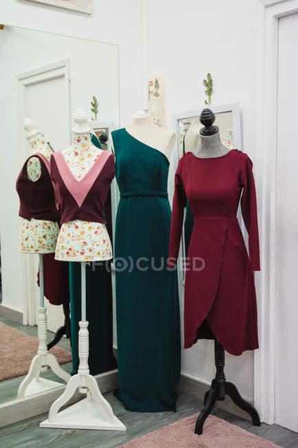 Манекены с модной традиционной одеждой помещены возле зеркала в углу швейной мастерской — стоковое фото