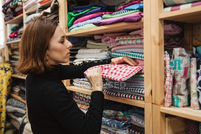 Seitenansicht einer erwachsenen Frau, die im Regal wühlt, während sie ein Stück Stoff für die Arbeit im Abstellraum der Schneiderei auswählt — Stockfoto