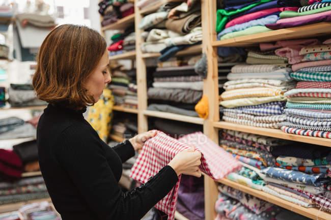 Бічний вид дорослої жінки бродить по полиці, вибираючи шматок тканини для роботи в сховищі кравця майстерні — стокове фото