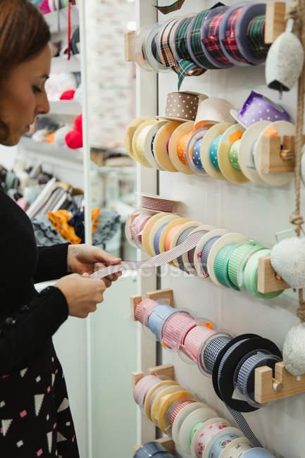 Vista lateral da costureira selecionando fitas enquanto estava perto de prateleiras na loja e compra de suprimentos de costura — Fotografia de Stock